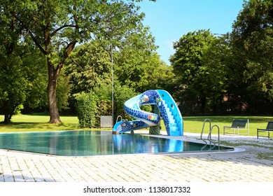 MUNICH, GERMANY -JULY 17, 2018 Wonderful summer weather and leisure time for children to  swim in a cute poll with slide at one of the popular swimming baths in Munich