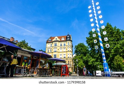 Munich, Germany - July 19: typical bavarian maypole with flag at the famous wiener platz in munich on July 19, 2018