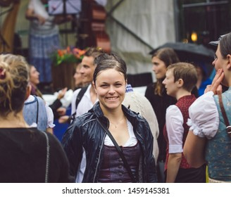 "Munich, Germany - July 21, 2019: People in traditional bavarian german ""tracht"" called dirndl dancing during the ""Kocherball"" event on very rainy wet bad weather sunday morning fun dance in puddle"