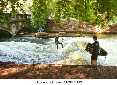 MUNICH, GERMANY - JULY 24, 2018 -  Munich, surfers in diving suit practice on the artificial wave on the Eisbach, small river across the Englischer Garten, in a summer morning