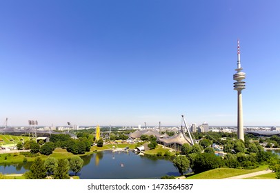 "Munich, Germany - July 24 2019 - northern city skyline behind olympic park ""Olympiapark"" and television tower ""Olympiaturm"" with lake and a yellow ferris wheel, seen from the park hill ""Olympiaberg"""