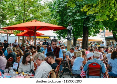 Munich, Germany - July 29, 2018: Locals and tourists enjoy beer and food at an open air beer garden in Viktualienmarkt in the historic centre of Munich, Germany