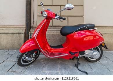 Munich, Germany - june 09, 2018: Iconic red Vespa,old fashioned Italian motorcycle, is parked on the street sidewalk in Munich center.