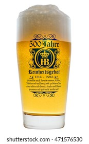Munich, Germany - June 11, 2016: Glass of cold Bavarian beer with frothy foam head backlit isolated on white with text 500 years of Reinheitsgebot - German Beer Purity Law