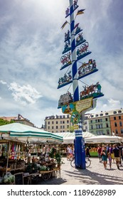 Munich, Germany - june 11: famous maypole at the Viktualienmarkt at a sunny day. It is a daily food market and a square in the center of Munich near Marienplatz on june 11, 2018