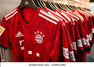 Munich, Germany - June 16, 2018 :  Adidas FC Bayern Munich T-Shirts, hanging on hanger, selling in Bayern Munich FC Bayern fan shop.