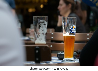 Munich, Germany - June 17, 2018 : Glasses of Schneider Weisse, classic German wheat beer, on the table. Selective focus.