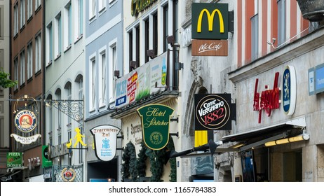 Munich, Germany - June 17, 2018 :  Various of brand logos, such as McDonalds, Paulaner beer, hotels, and restaurant logos, hanging on the building wall at Marienplatz. Advertising signs
