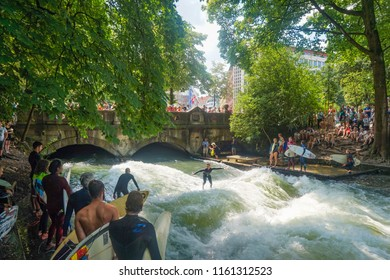 Munich, Germany - June 2018: Surfers on the Eisbach in the Englischer Garden with many spectactors. This river flows through the Englischer Garden and is a popular river surf spot