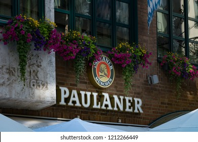 Munich, Germany - June 21, 2018 : Paulaner, a German brewery and high quality brand beers, logo sign hanging on brick wall at restaurant near Marienplatz.