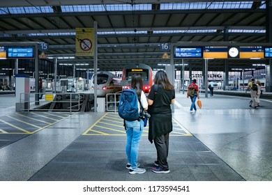 Munich, Germany - June 21,2018 : Two young Asian travelers with backpack and DSLR camera at Munich Hauptbahnhof station. concept of self-traveling. Backpacker. budget traveler.