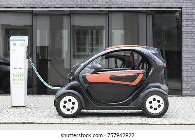 Munich, Germany- June 25, 2016: Electric car, Renault, being recharged at plug-in station in front of modern office building.