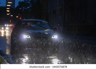 Munich, Germany - June 27. 2019: Heavy rainstorm in munich city night time car driving by in lots of rain water reflecting in light