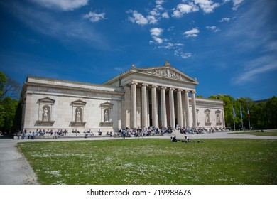 MUNICH, GERMANY - MAY 11, 2017: Koenigsplatz with Glyptothek in spring on a sunny day with blue sky. People like to relax in front of the statue collection.