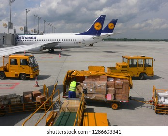 Munich, Germany - May 17, 2006: Postal parcels are loaded into an airplane at the airport Franz Josef Strauss, while to machines of the company Lufthansa are waiting at the terminal in background