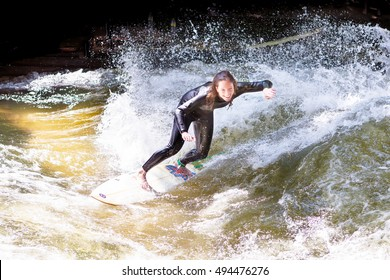 MUNICH, GERMANY   MAY 24, 2011: Experienced Female Surfer Riding A Wave In
