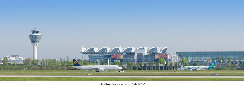 Munich, Germany - May 6, 2016: Panoramic view of Munich international airport with taxiing passenger airplanes and terminal and air traffic control tower