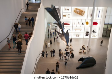 Munich, Germany - November 2016: The interior of the Pinakothek der Moderne (modern art museum), with tourists walking around and viewing the various art installations and displays