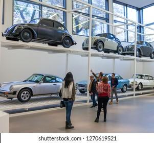Munich, Germany - November 2016: Tourists look at vehicles from different eras inside the Pinakothek der Moderne, a modern art museum in Munich.