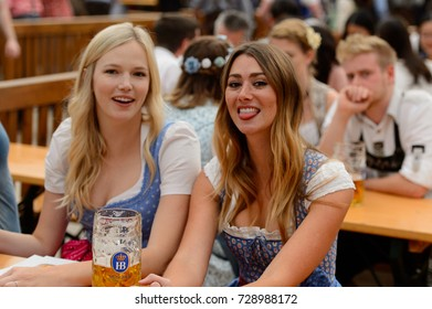 MUNICH, GERMANY - OCT 2, 2017: Unidentified beautiful girls in traditional Bavarian costume drink beer at the Octoberfest,  the world's largest festival