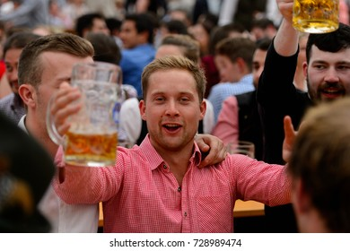 MUNICH, GERMANY - OCT 2, 2017: Unidentified young man in traditional Bavarian costume drinks beer at the Octoberfest,  the world's largest festival