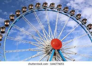 MUNICH, GERMANY - OCTOBER 1, 2019 Giant ferris wheel with Bavarian style booths at the Oktoberfest in Munich