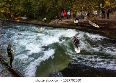 Munich, Germany - October 15, 2018: Surfer in the city river, Munich is famous for people surfing in urban enviroment called Eisbach