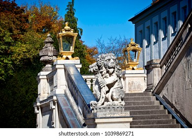 MUNICH, GERMANY - OCTOBER 16, 2017  - Golden lanterns and a carved lion, symbol of Bavaria,  decorating the staircase of the baroque  Nymphenburg palace, summer residence of the rulers of Bavaria