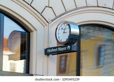 Munich, Germany - October 20, 2017:  Sign of jewelry store Herbert Mayer with a street clock