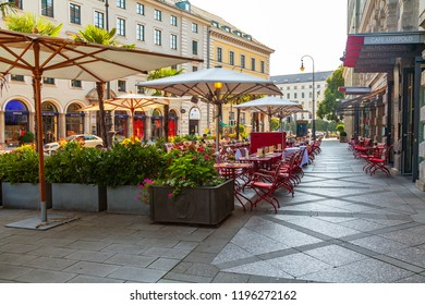 Munich, Germany, on August 16, 2018. Little tables of cafe on the city street wait for visitors