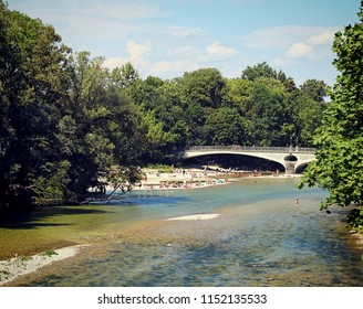 Munich, Germany - people take a bath in the clean waters of Isar river near  Kabelsteg bridge in Munich center city