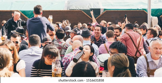 Munich, Germany - Sep 28, 2019: People sitting at famous bavarian Oktoberfest drinking beer and having fun at munich festival