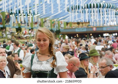 MUNICH, GERMANY - SEPT. 21, 2014:  Oktoberfest Crowds of visitors at the Spatenbrau Tent celebrating the festivities with Smiling Waitress. The Festival runs from Sept. 20 - Oct. 5  in Munich, Germany