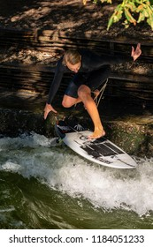 MUNICH, GERMANY - SEPT 8, 2018: Man surfing in the waves of the Eisbach River in Munich. It forms a standing wave right at the entrance of the Englischer Garten and is a popular surfers meeting point