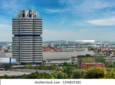 MUNICH, GERMANY - SEPT 8, 2018: The tower of the BMW (BMW-Vierzylinder or BMW-Turm), in the background the Allianz Arena, soccer stadium (Fussball Arena Munchen, Schlauchboot).