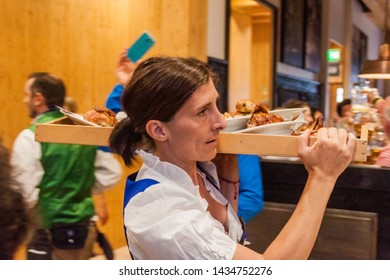 MUNICH, GERMANY - SEPTEMBER 17, 2016: Waitress carrying meaty platters at the Oktoberfest in Munich