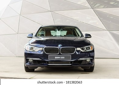 MUNICH, GERMANY - SEPTEMBER 19, 2012: New model BMW 335i in dark blue against modern design surface.