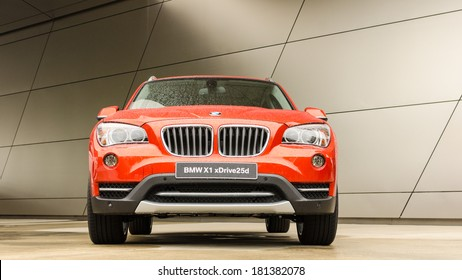 MUNICH, GERMANY - SEPTEMBER 19, 2012: New model BMW X1 SUV against modern design building. Orange wet car standing on podium after rain.