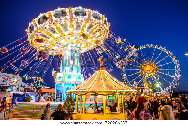 MUNICH, GERMANY - SEPTEMBER 21: people and fairground rides at the biggest folk festival in the world - the octoberfest on september 21, 2017 in munich.