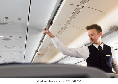 Munich, Germany - September 21th, 2017: A male Flight attendant is checking the overhead compartments of an Airbus 330 - 300 of Lufhansa Airlines defore take off.