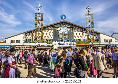MUNICH, GERMANY - SEPTEMBER 23, 2012: Oktoberfest, Munich: One of the big beer tents. In the foreground, people are walking along, partly dressed in traditional costumes.