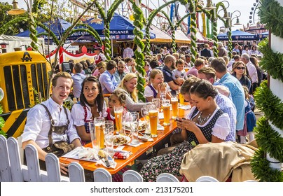 MUNICH, GERMANY - SEPTEMBER 23, 2012: Oktoberfest munich: People dressed in traditional costumes are sitting in the beergarden.