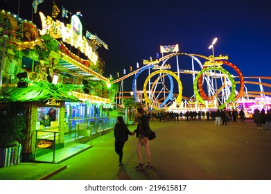 MUNICH, GERMANY - SEPTEMBER 23, 2014: The Oktoberfest in Munich is the biggest beer festival of the world. The visitors have lot of fun with many amusement huts and shops for food and souvenirs.