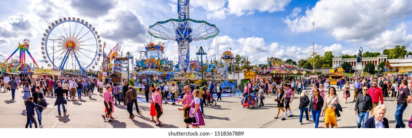 Munich, Germany - September 24: visitors, beertents and fairground rides on the oktoberfest in munich at September 24, 2019