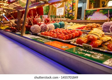 Munich, Germany - September 26, 2015: Sales stall for takeaway food (candied sweets around apples, strawberry, grapes and nuts) at Oktoberfest