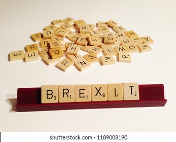 Munich, Germany - September, 26 2018: Scrabble letters spelling the word BREXIT. Scrabble tiles on the stand concerning the current political topic in the UK. Mixed scrabble tiles in the background.