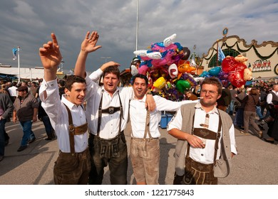 MUNICH / GERMANY - SEPTEMBER 26th, 2008: Cheering visitors to Oktoberfest dressed in Lederhosen (Bavarian costumes)