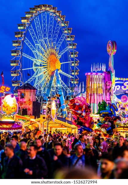Munich, Germany - September 27: visitors, beertents and fairground rides on the oktoberfest in munich at September 27, 2019
