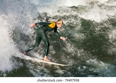 MUNICH, GERMANY - SEPTEMBER 28: Unidentified surfer riding the Eisbach standing wave on September 28, 2009 in Munich, Germany. The small man-made river runs through the Englischer Garten park.