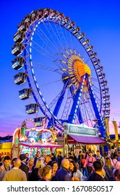 Munich, Germany - September 28: visitors, beertents and fairground rides on the oktoberfest in munich at September 28, 2019